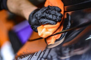 Mechanic polishing car wearing gloves