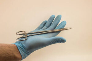 Medic holding scissors with gloved hand